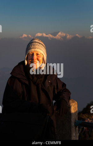 India, West Bengal, Darjeeling, Tiger Hill, western woman tourist posing in front of Kangchenjunga at dawn - Stock Photo