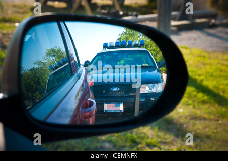Police Ford car in side mirror - Stock Photo