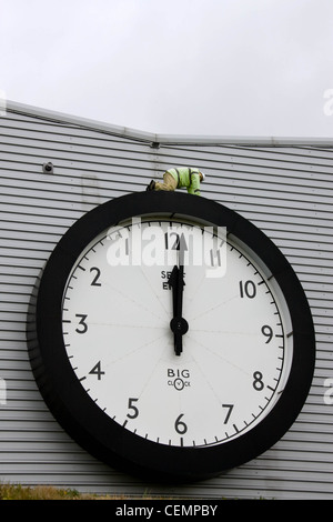 Model figure on top of a giant clock on the side of an industrial building - Stock Photo