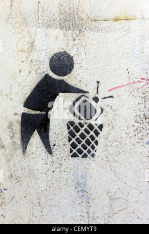 graffiti on wall near Tahrir Square, Cairo, Egypt with image of television being dumped in wastebasket - Stock Photo