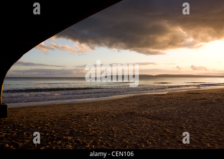 sea sunset taken from underneath a pier - Stock Photo