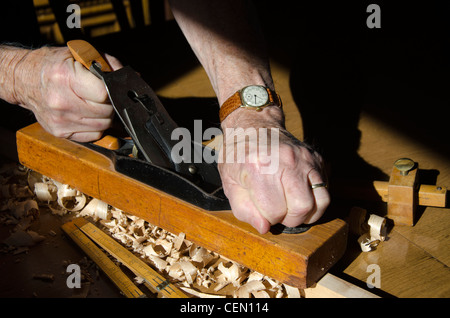 Close up of hands gripping an old wood Block Plane shaving a workpiece to size. Shavings and other old tools are - Stock Photo