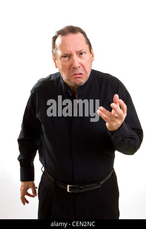Grumpy old man dressed in black stretches out his hand with a look of contempt and anger. - Stock Photo