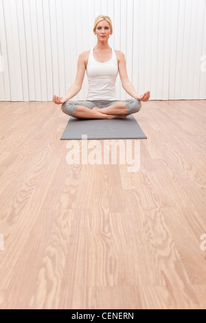 A beautiful young blond woman sitting cross legged in a yoga position at a gym - Stock Photo