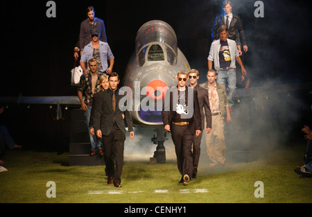 Iceberg Milan Menswear S S Group of male in Iceberg outfits, surrounding a jet, walking towards the camera, on green - Stock Photo