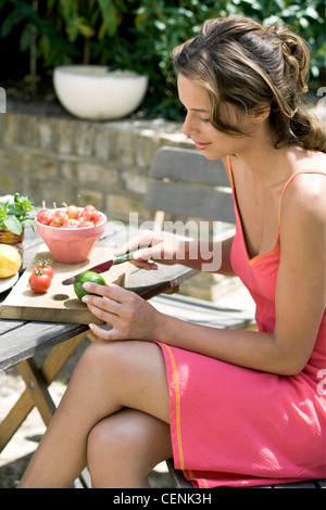 A DayYourself: Profile of female brunette hair tied back loosely wearing short pink sundress orange detail, sitting - Stock Photo