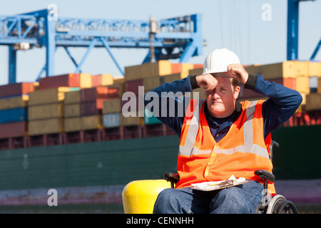 Transportation engineer in a wheelchair recording data for shipping containers and experiencing hot sun - Stock Photo