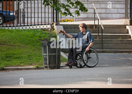 Man with spinal cord injury in a wheelchair putting trash in receptacle at public park - Stock Photo