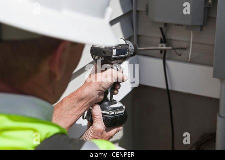 Communications worker drilling access hole through exterior wall - Stock Photo