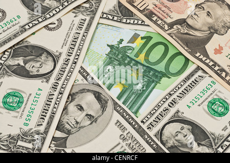 Many U.S. Dollar bills lying side by side. In the middle lies a 100 Euro bill. - Stock Photo