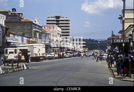 Busy scene on Kenyatta Avenue Nakuru Kenya with people traffic vehicles men women parked cars shops Chemists - Stock Photo