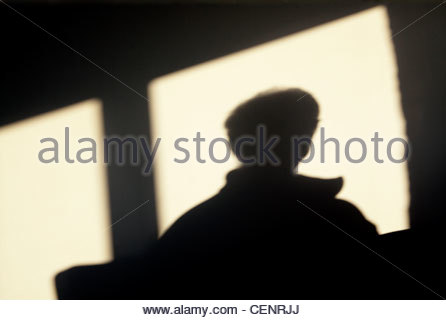 silhouette of a person looking out of a window - Stock Photo