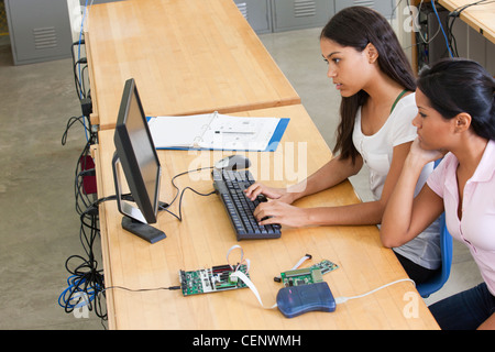 Engineering students at computer using in-circuit emulator - Stock Photo