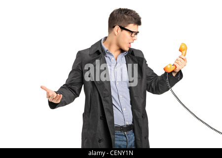 A surprised male holding a telephone tube isolated on white background - Stock Photo