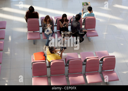People waiting in an airport lounge - Stock Photo