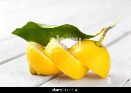 Sliced Lemon on White Wood - Stock Photo