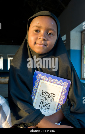 Muslim girl with a book in Bwejuu village east coast of Zanzibar Tanzania - Stock Photo