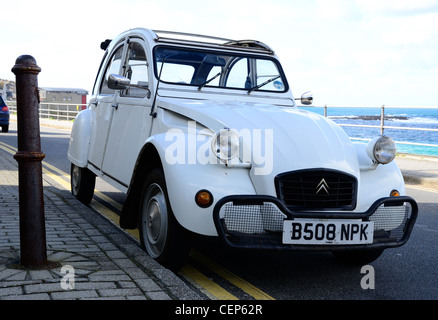 Citroen 2CV parked on seafront at Sennen Cove, Penwith, Cornwall - Stock Photo