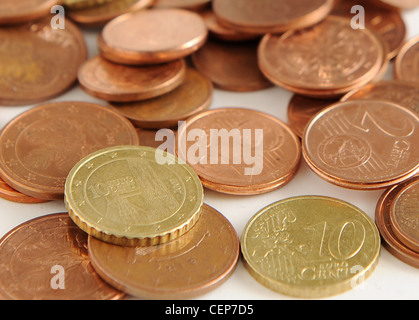 A still life image of Euro cent coins scattered on the white table - Stock Photo