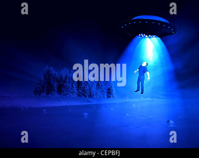 Man being abducted by aliens on a winter night. - Stock Photo
