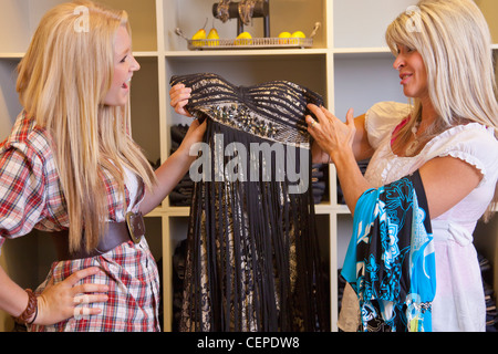 mother and daughter shopping for clothes at a boutique; edmonton, alberta, canada - Stock Photo