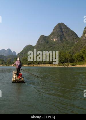 Man On A Raft In A River; Guangxi Zhuang,China - Stock Photo