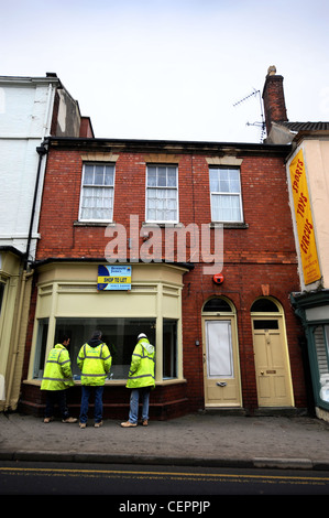 Construction workers look into an unoccupied shop in temporary use as an art gallery in Dursley, Gloucestershire, - Stock Photo