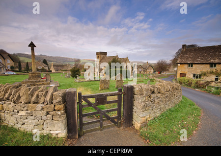 Cotswold stone cottages and St Barnabas Church in the village of Snowshill in Gloucestershire, UK - Stock Photo