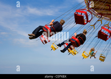 People enjoying a ride on a traditional Chair-o-plane carousel at a fair in Whitstable. - Stock Photo