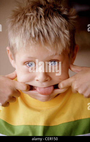 Male child blonde spiky hair wearing yellow and green t shirt fingers pulling each side of mouth tongue sticking - Stock Photo