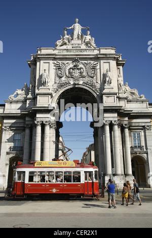Rua Augusta Arch and a Yellow Bus Sightseeing Tour Tram, Praça do Comércio, Lisbon, Portugal - Stock Photo