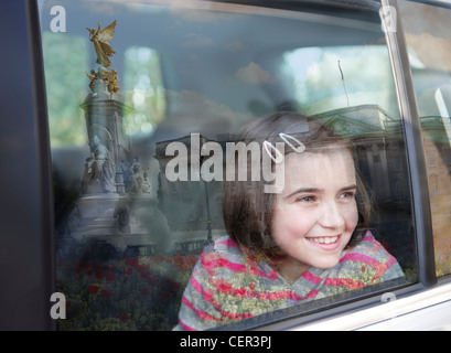 A young girl looking out of a  car window at Buckingham Palace. - Stock Photo