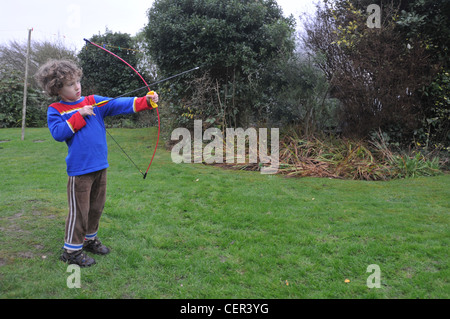 A six year old boy plays with a bow and arrow - Stock Photo