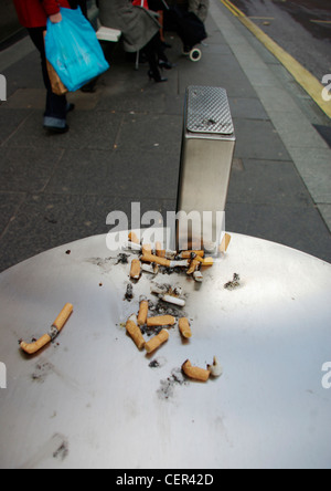 Cigarette ends on top of a litter bin. - Stock Photo