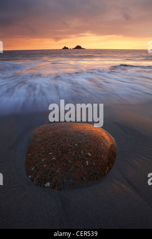 The tide rolling onto Porth Nanven beach towards a large ovoid rock in the foreground at sunset. - Stock Photo