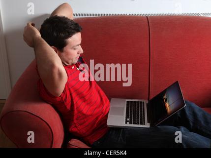 Profile of a single man using a laptop. - Stock Photo