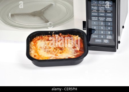 Cooked lasagna readymeal in black plastic tray in front of microwave oven with door open. - Stock Photo