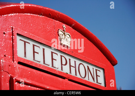 Detail of a traditional red telephone box set against a blue sky in London. - Stock Photo