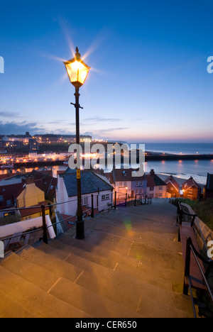A traditional street light illuminates the 199 steps leading down towards the old town of Whitby. - Stock Photo