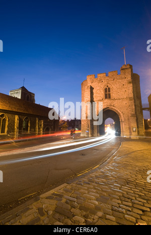 The Westgate Tower in Canterbury lit up at night with trials of light from passing traffic. - Stock Photo