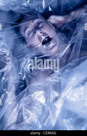 Woman under plastic covering - Stock Photo