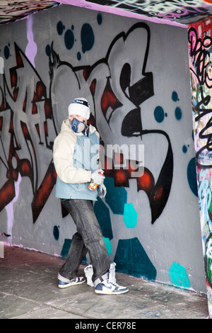 Young Male spray painting in designated space on Southbank - London - UK - Stock Photo