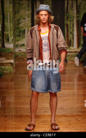 D&G Milan Menswear S S Casual wear: checked bomber jacket and baggy Bermuda jean shorts slippers Wood floand forrest - Stock Photo