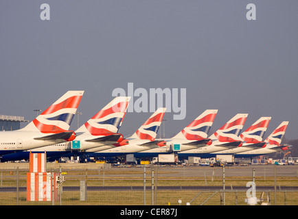 A row of tail fins from British Airways Jumbo jets outside a terminal at Heathrow airport. - Stock Photo