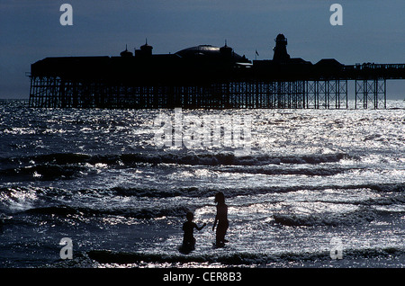 The silhouettes of two children paddling in the sea by Brighton Pier.