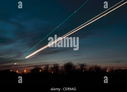 Light trail from an aircraft coming in to land at Heathrow airport at dusk. - Stock Photo