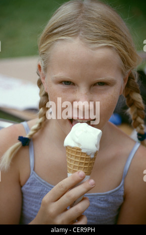 MFemale child with blonde hair off face in two plaits eating vanilla ice cream cone looking to camera - Stock Photo
