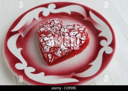A heart shaped cookie on a plate. - Stock Photo