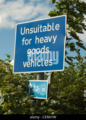 WARNING ROAD SIGN ON COUNTRY ROAD UNSUITABLE FOR TRUCKS WITH BICYCLE ROUTE MARKER IN HEDGE - Stock Photo