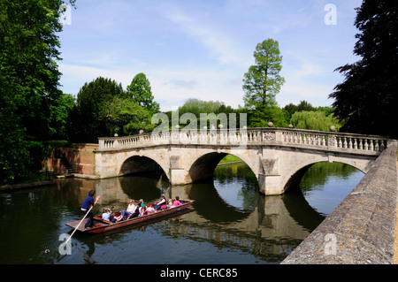Tourists enjoying a trip along the River Cam, about to go under Clare bridge in a punt. - Stock Photo